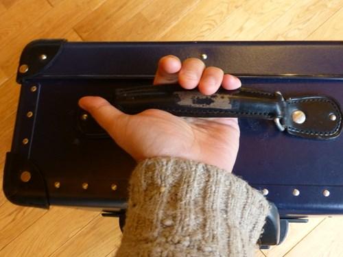 グローブ・トロッター(globe trotter)のスーツケース・サーフライダーの取っ手を掴む