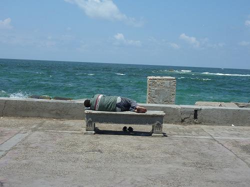 エジプト・アレクサンドリアの海岸沿いのベンチで眠る男