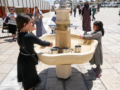 エルサレム(イスラエル)の嘆きの壁の手洗い場で手を洗う少女