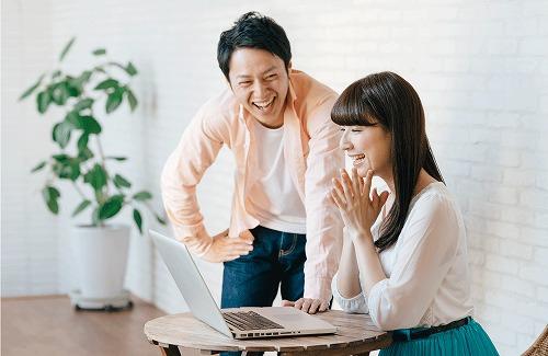 パソコンの画面を見て喜ぶ恋人