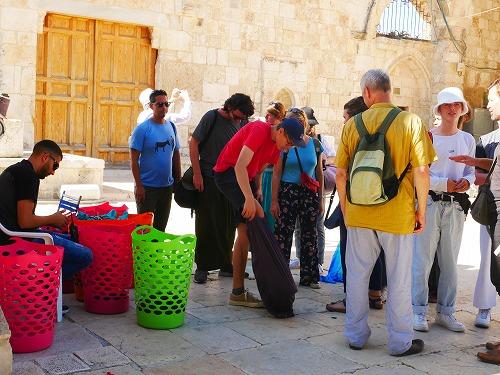エルサレム(イスラエル)の神殿の丘入口で布をまく人々
