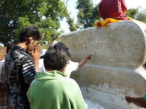 タイ・アユタヤ遺跡のワット・ヤイ・チャイ・モンコンの寝釈迦の足の裏に硬貨を貼り付ける
